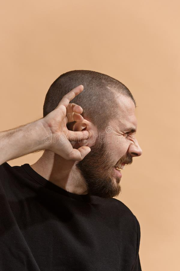 The Ear ache. The sad man with headache or pain on a pastel studio background. Sore ear. Ear ache concept. The sad crying man with headache or pain on trendy royalty free stock images