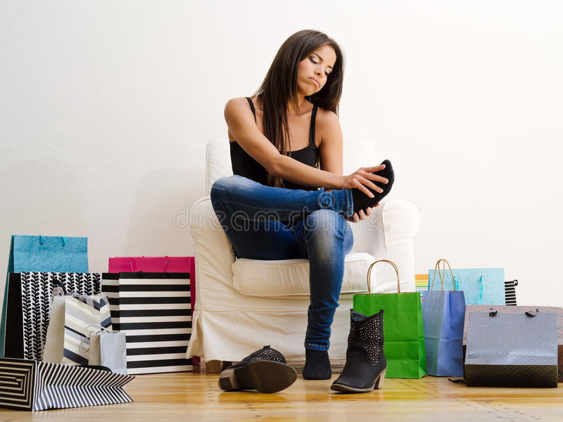 Sore feet from shopping. Photo of a young beautiful female sitting on a chair surrounded by shopping bags and rubbing her sore feet stock photo
