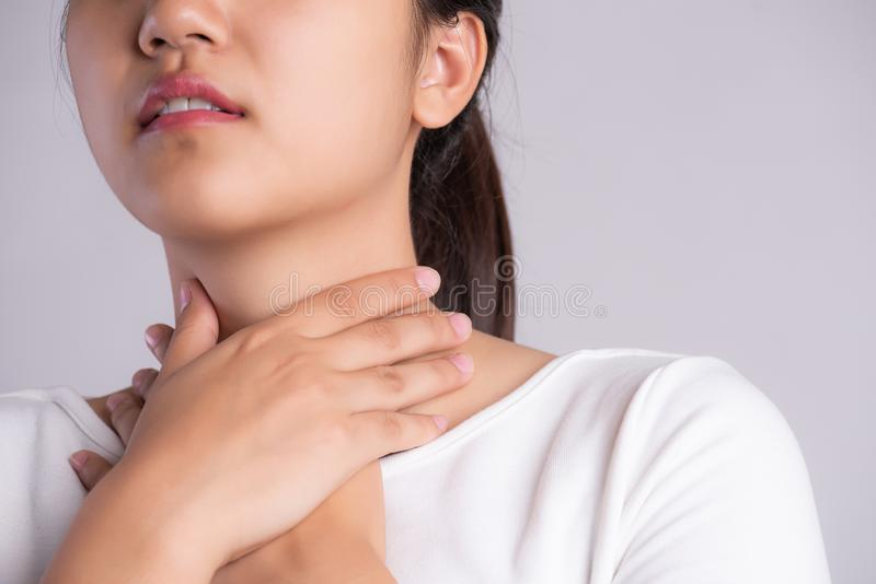 Sore Throat. Closeup Of Beautiful Young Woman Hand Touching Her Ill Neck. Healthcare and medical concept royalty free stock images