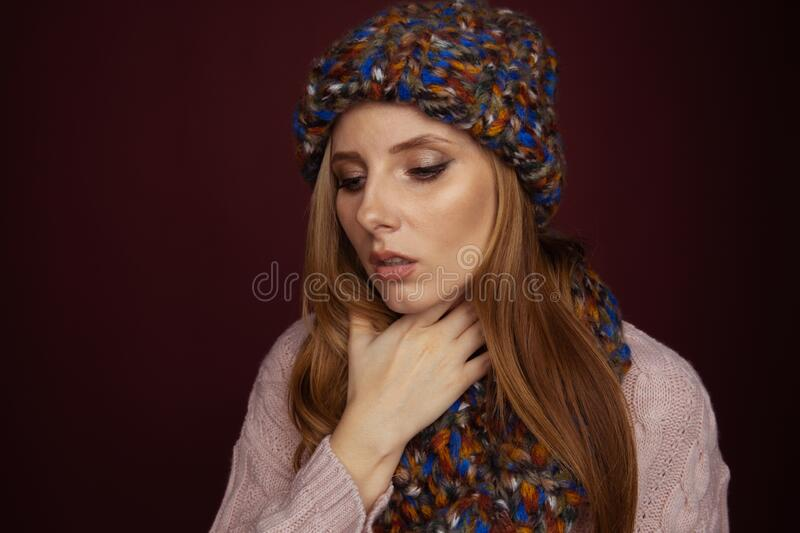 Sore throat concept. Sick woman in hat and scarf holding her nech and felling bad. stock photos