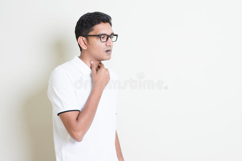 Sore throat. Portrait of Indian guy sore throat, hand on neck clearing throat. Asian man standing on plain background with shadow and copy space. Handsome male royalty free stock photography