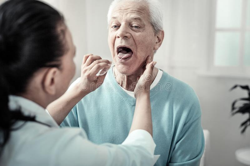 Serious aged man showing his tongue and doing nurses orders. royalty free stock photography