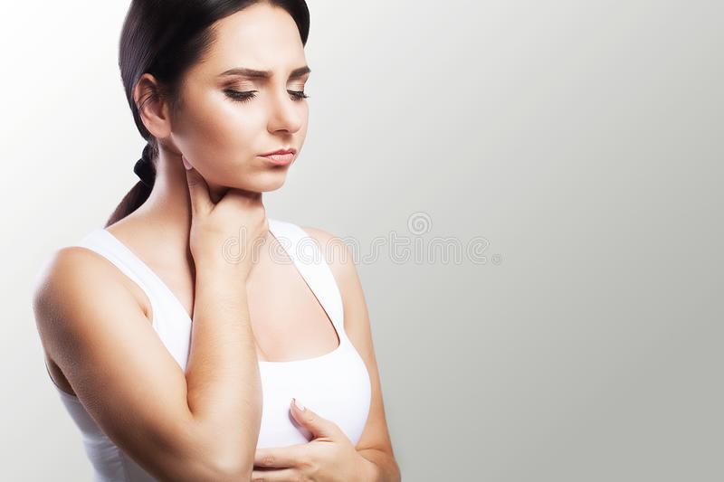 Sore throat. Sick woman, flu Young beautiful woman with sore throat. Feeling painful in the throat. The concept of health. On a gr. Ay background stock images