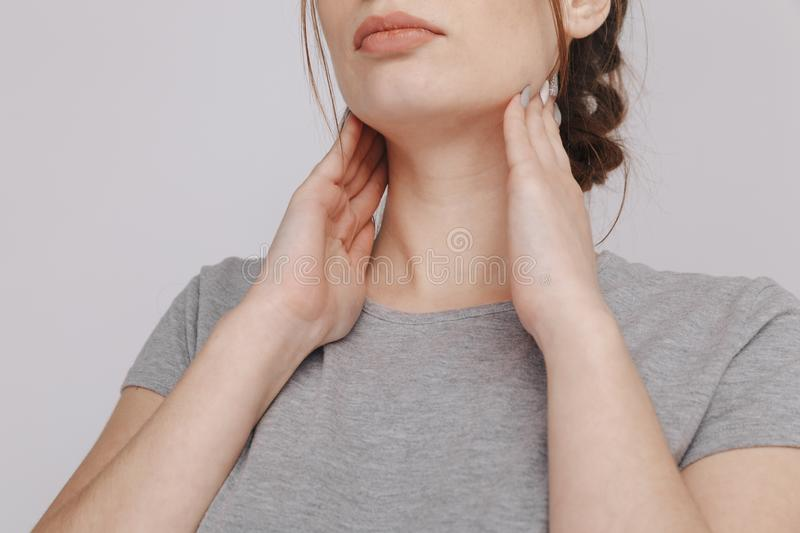 Sore throat. Woman holding hands on her throat. Heartburn concept. royalty free stock photography