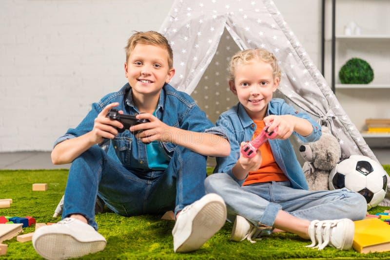 sorella allegra e fratello che giocano con le leve di comando vicino al wigwam fotografia stock libera da diritti