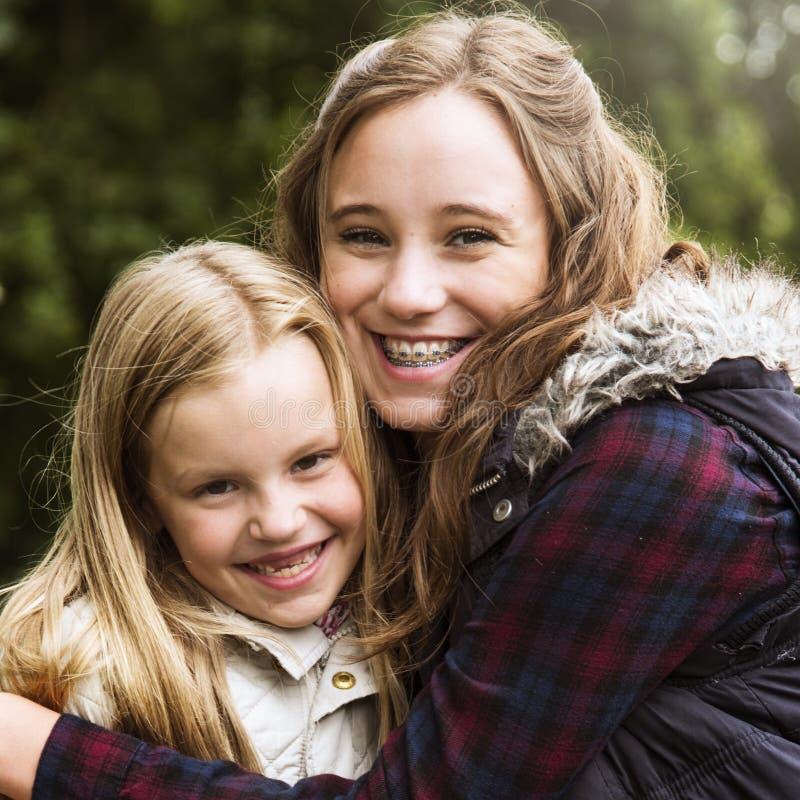 Sorella concetto delle ragazze di Hug Togetherness Outdoors fotografia stock libera da diritti