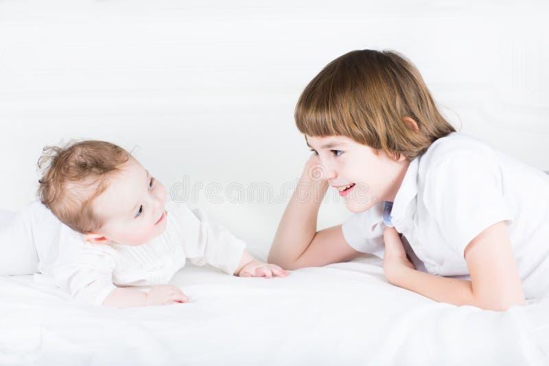 Sorella del bambino e del fratello che gioca su un letto bianco fotografia stock libera da diritti