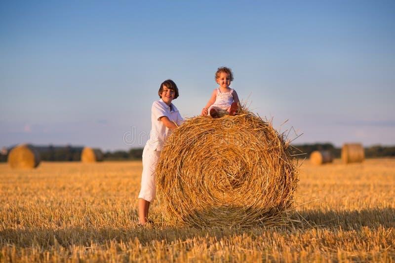 Sorella del bambino e del fratello che gioca in un campo delle balle di fieno fotografia stock libera da diritti