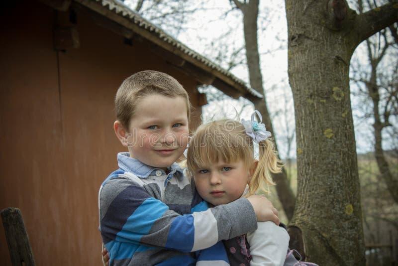 Sorella del fratello che abbraccia nel villaggio immagine stock