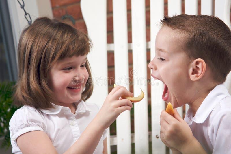 Sorella e fratello che mangiano un Apple immagini stock libere da diritti
