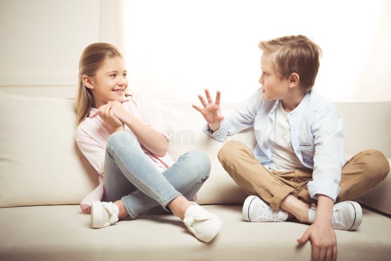 Sorella e fratello che parlano insieme mentre sedendosi sul sofà a casa fotografia stock
