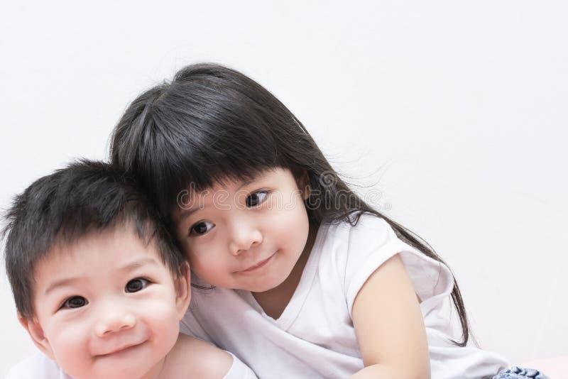 Sorella e fratello del bambino in camicia bianca che si abbraccia immagine stock libera da diritti