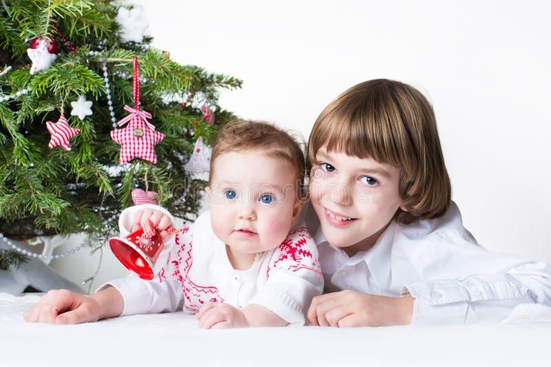 Sorella felice del bambino e del fratello che gioca insieme sotto il Natale immagini stock libere da diritti