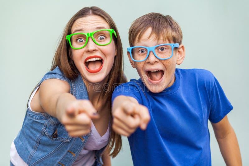 Sorella più anziana ed suo fratello con le lentiggini, posando sopra il fondo blu-chiaro insieme, esaminando macchina fotografica fotografie stock libere da diritti