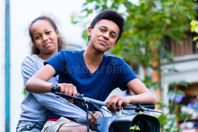 Sorella sorridente che si siede con suo fratello che guida una vecchia bici immagini stock