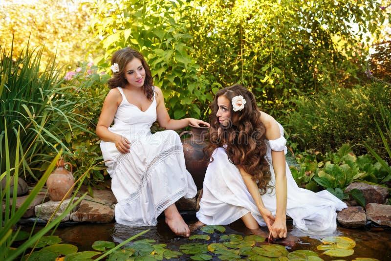 Sorelle acqua di tiraggio da uno stagno fotografia stock
