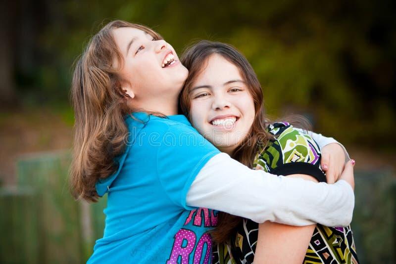 Sorelle amorose che abbracciano e che sorridono fotografie stock libere da diritti