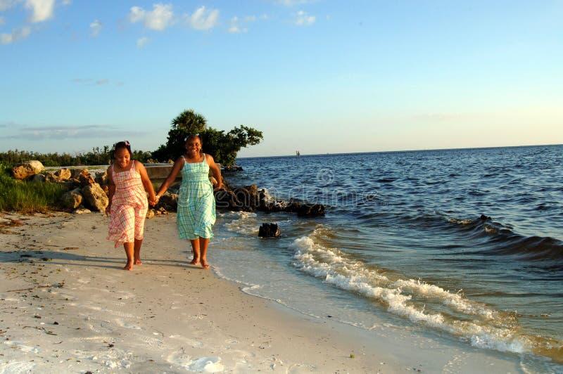 Sorelle che funzionano alla spiaggia immagini stock libere da diritti