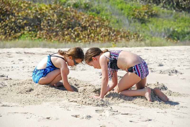 Sorelle che giocano alla spiaggia immagini stock
