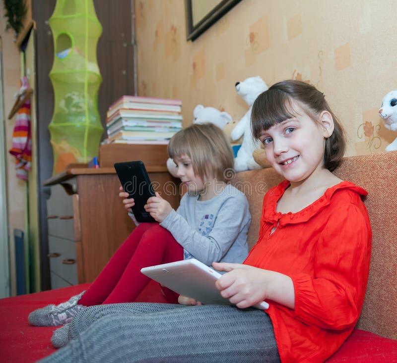 Sorelle che giocano sulle compresse nella stanza del ` s dei bambini immagini stock