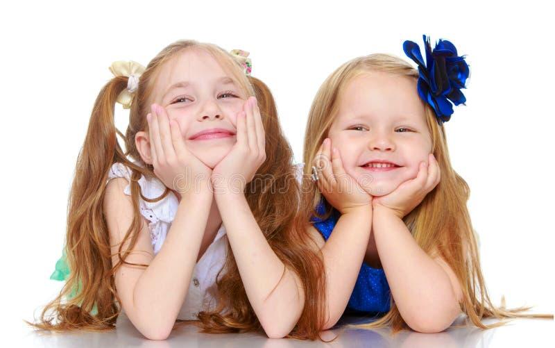 Sorelle che si trovano sul pavimento fotografie stock