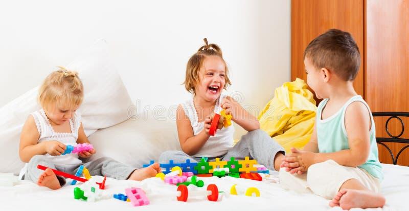 Sorelle e fratello divertendosi sul letto immagine stock