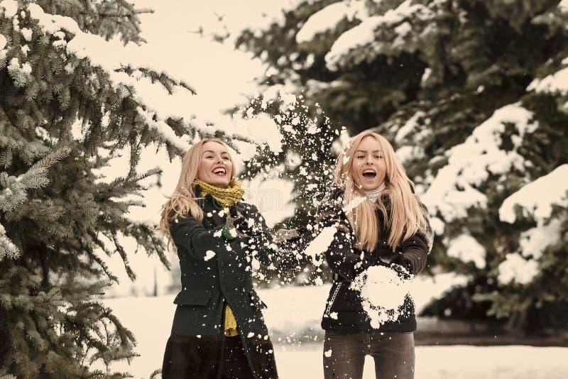 Sorelle felici che giocano le palle di neve in foresta il giorno di inverno immagine stock