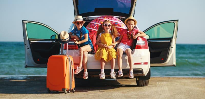 Sorelle felici degli amici di ragazze dei bambini sul giro dell'automobile al viaggio di estate immagine stock