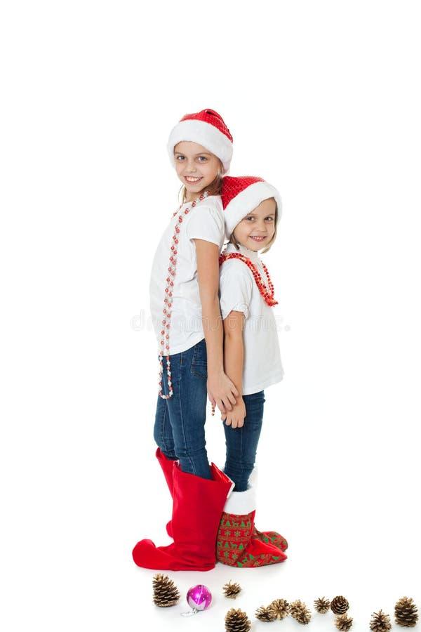 Sorelle felici nei cappelli di Santa e nei calzini del regalo fotografia stock libera da diritti