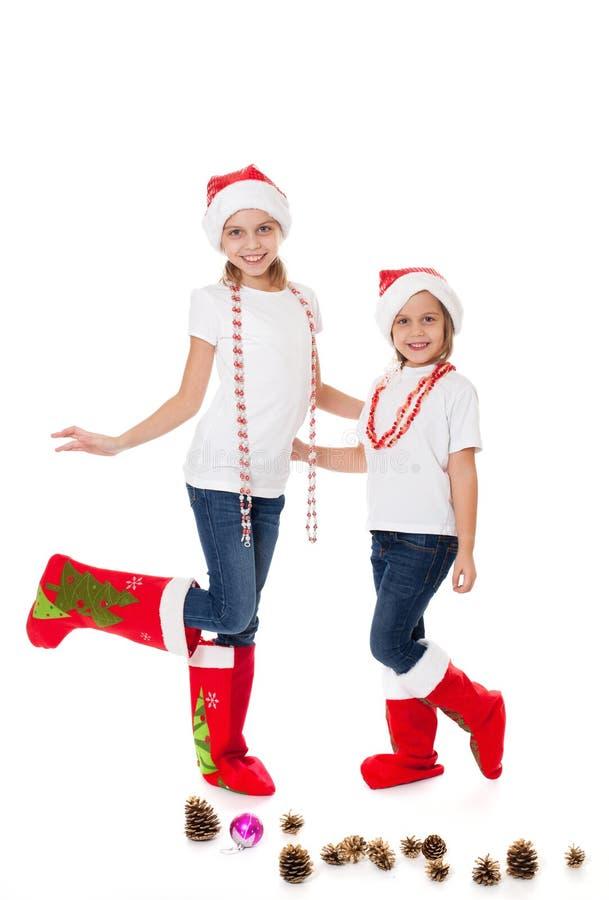 Sorelle felici nei cappelli di Santa e nei calzini del regalo immagine stock libera da diritti