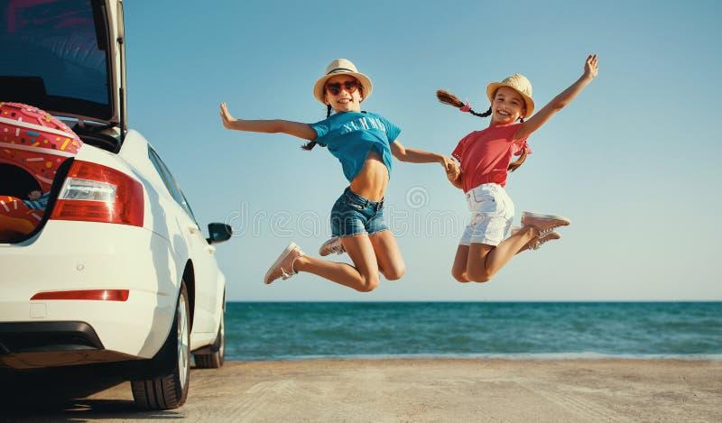 Sorelle gemellate delle ragazze felici dei bambini sul giro dell'automobile al viaggio di estate immagini stock