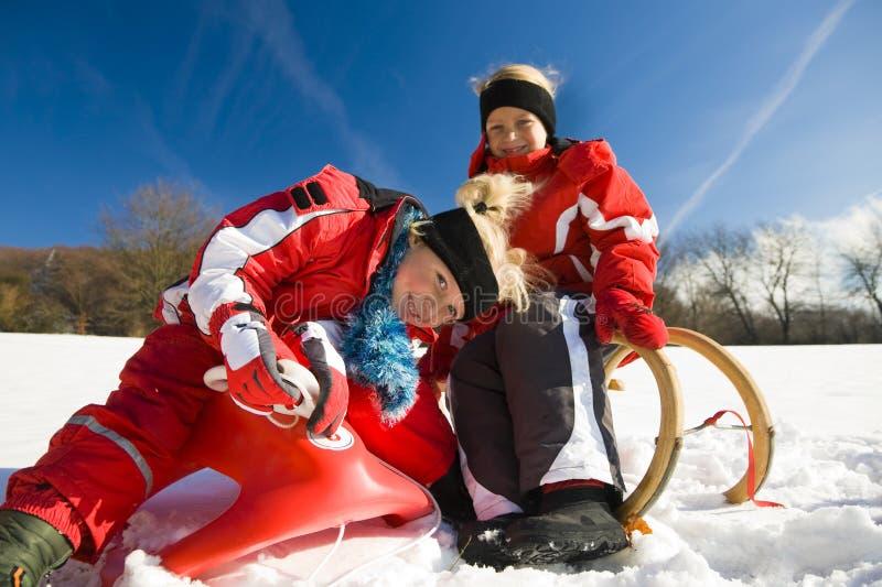 Sorelle in neve sul toboggan immagini stock libere da diritti