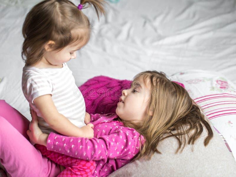 Sorelle ragazze che si trovano sul letto immagine stock
