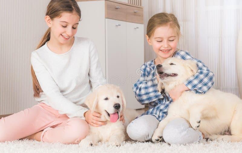 Sorelle sorridenti che si siedono con i cuccioli del documentalista fotografia stock