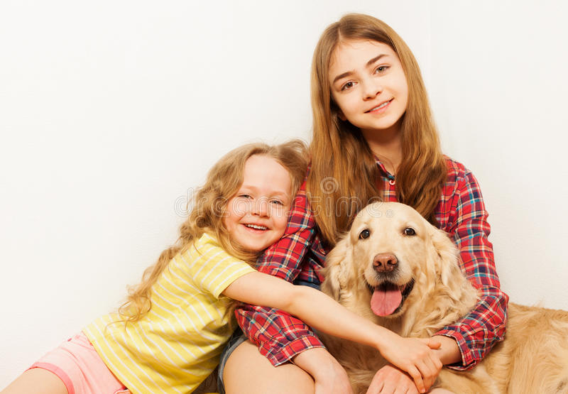 Sorelle sorridenti con il loro golden retriever adulto fotografia stock