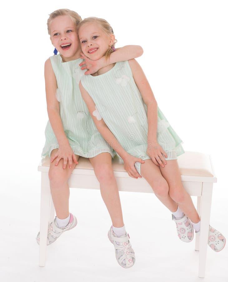Sorelle sveglie divertendosi seduta su una sedia. fotografie stock