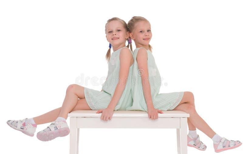 Sorelle sveglie divertendosi seduta su una sedia. immagini stock libere da diritti