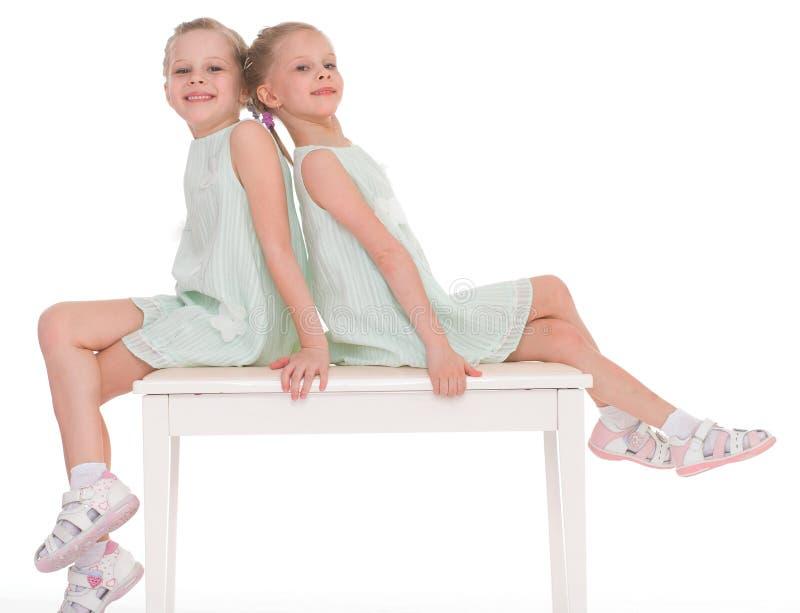 Sorelle sveglie divertendosi seduta su una sedia. fotografia stock