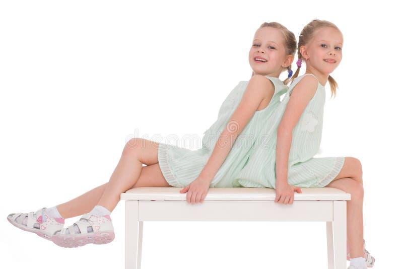 Sorelle sveglie divertendosi seduta su una sedia. immagine stock libera da diritti