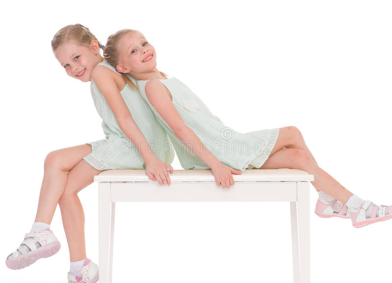 Sorelle sveglie divertendosi seduta su una sedia. fotografia stock libera da diritti