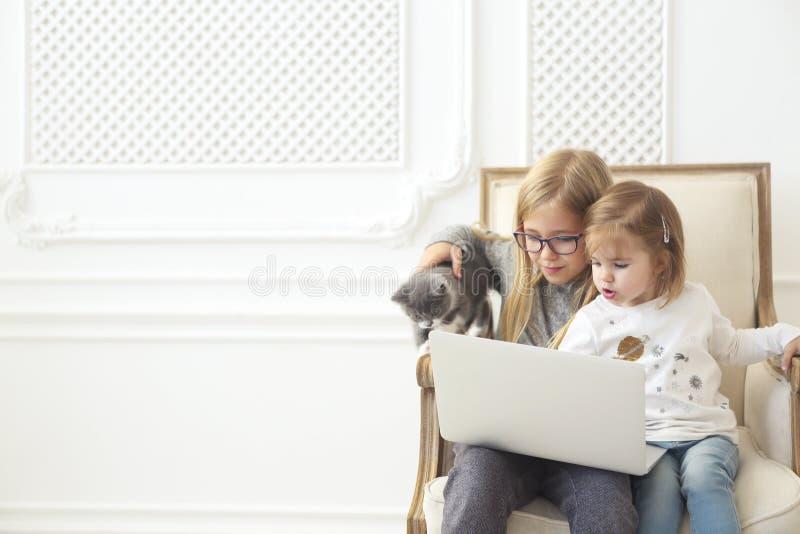 Sorelline adorabili che per mezzo del loro computer portatile del computer insieme al loro gattino fotografia stock