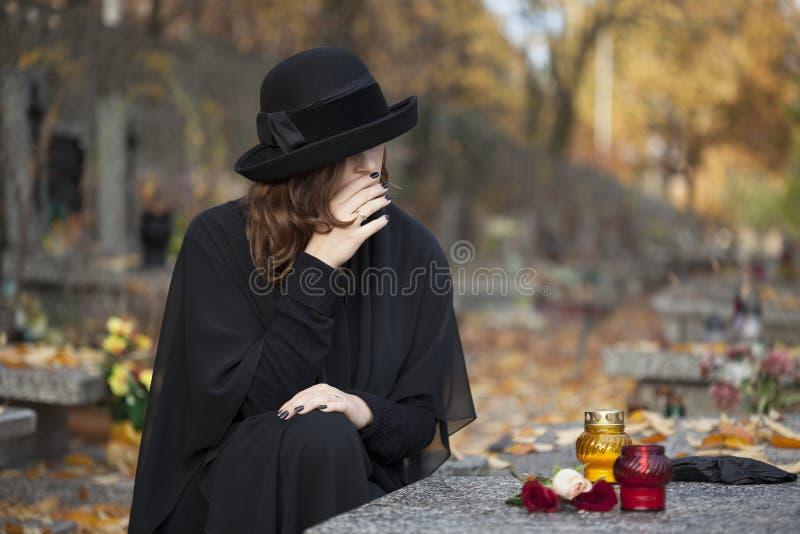 Sorgen machende Frau am Friedhof stockbilder