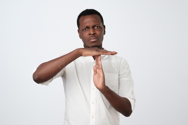 sorgen Sie sich, hübschen afrikanischen jungen Mann im weißen Hemd plädierend, stehend, Kamera betrachtend und TIMEOUTgestenzeich stockfotografie