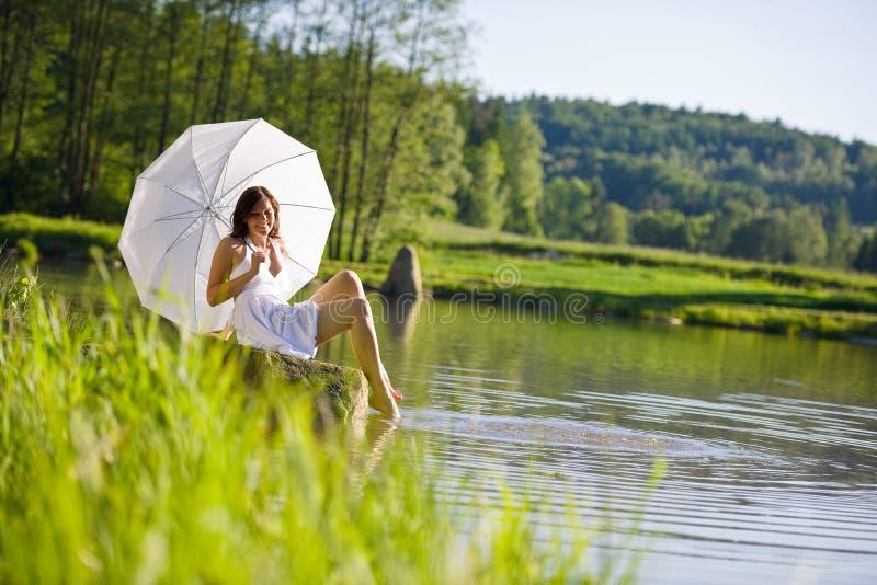 Primavera - donna romantica felice che si siede dal lago fotografie stock libere da diritti
