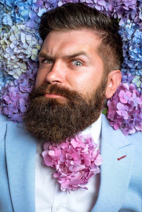 Sorgente il giorno delle donne maschio con i fiori dell'ortensia Pantaloni a vita bassa maturi con la barba Capelli e pelle sani  immagini stock