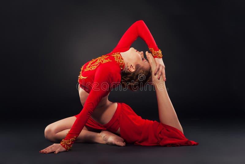 Sorgeous sportieve vrouw in rode kleding die yogaoefening doen stock afbeelding