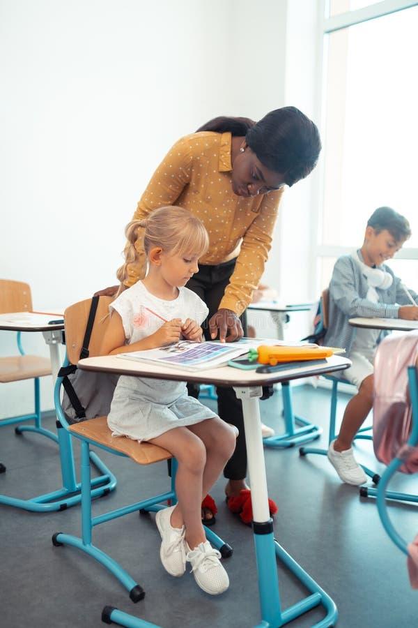 Sorgfältiges blond-haariges Mädchen, das aufmerksam auf Lehrer hört lizenzfreie stockbilder