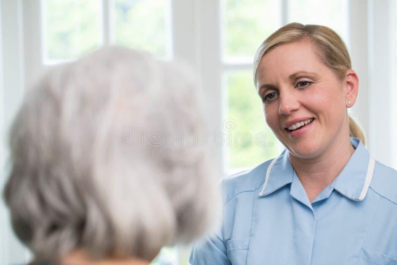 Sorgfalt-Arbeitskraft, die zu Hause mit älterer Frau spricht lizenzfreie stockbilder