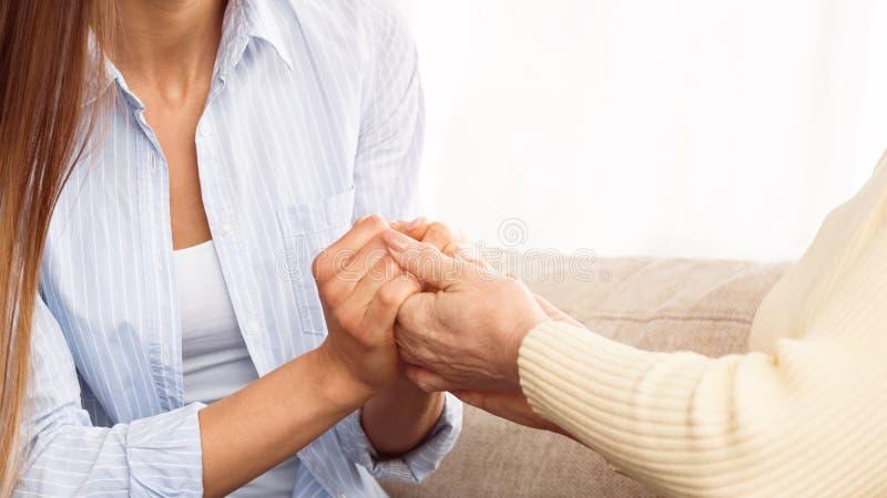 Sorgfalt zu den älteren Leuten Tochterholding-Mutterhände stockfotografie
