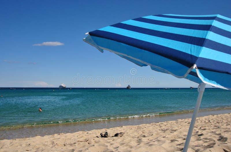 Sorglose Ferien: gestreifter Strandschirm, Flipflops auf dem Sand und helles blaues Meer stockbilder
